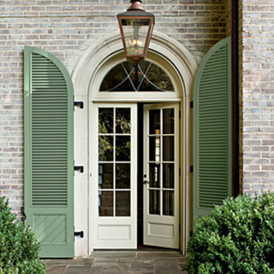Love these door length shutters on this painted brick home