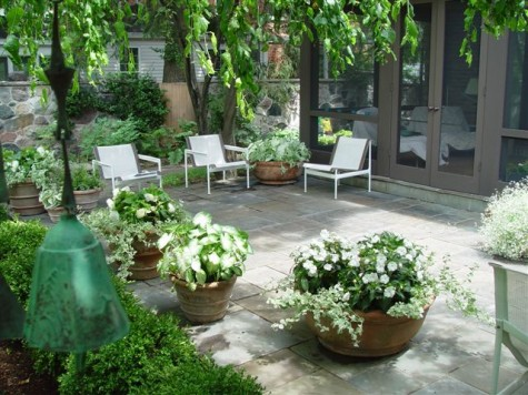 Paver patio with white chairs and white floral pots