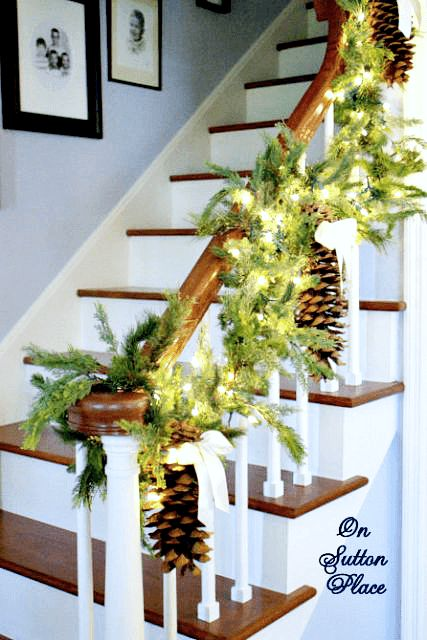 pretty holiday staircase with lights and pinecones - Christmas Staircase