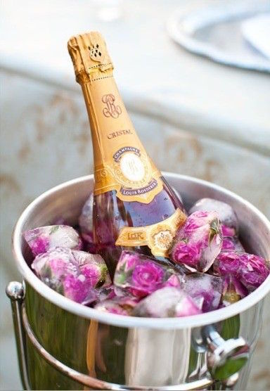 Rose Petal Ice Cubes are chilling this bottle of champagne in style. Read the post for more Valentine's Day Party Decorations
